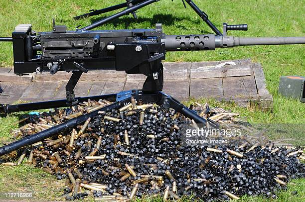 A .50 Caliber Browning Machine Gun with a pile of spent cases and links.