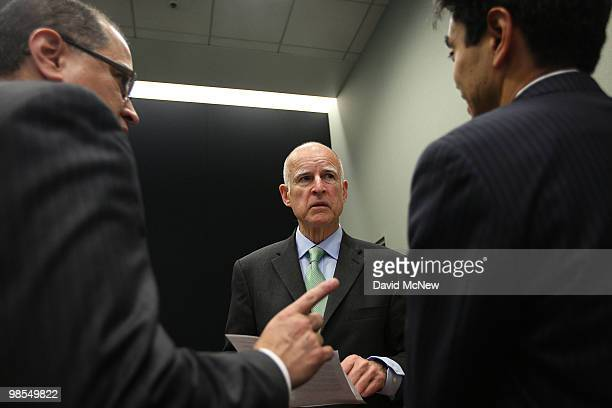 California Attorney General and gubernatorial candidate Jerry Brown speaks with his attorneys as he prepares to address a press conference to...