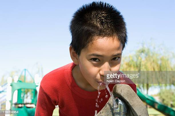 USA, California, Boy (12-13) at drinking fountain