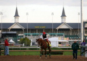 California Chrome walks off the track with trainer Art Sherman in front of the twin spires during early morning workouts at Churchill Downs on May 1...
