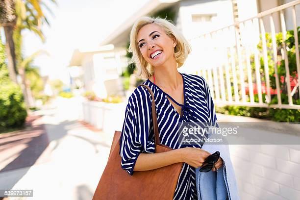 USA, California, Costa Mesa, Woman wearing striped blouse walking street and smiling