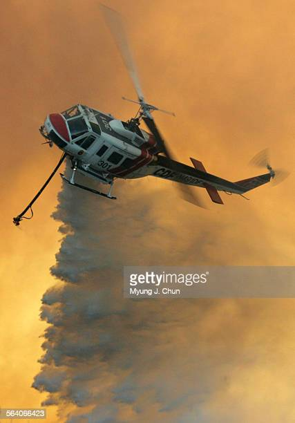 A California Department of Foresty helicopter makes a water drop on a brush fire burning close to homes on Avenida de Santiago in Anaheim Hills on...