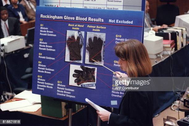 California Department of Justice criminalist Renee Montgomery points to blood spots found on the leather glove at O J Simpson's Rockingham estate...