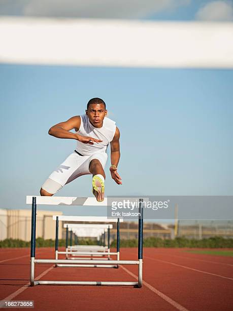 USA, California, Fontana, Boy (12-13) hurdling on running track