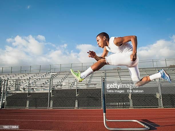 USA, California, Fontana, Boy (12-13) hurdling on running track