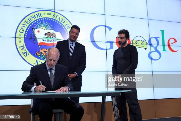 California Gov Jerry Brown signs State Senate Bill 1298 as California State Sen Alex Padilla and Google cofounder Sergey Brin look on at the Google...