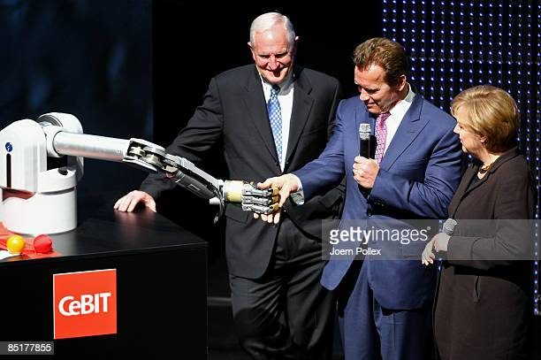 California Governor Arnold Schwarzenegger shakes hands with a robotic arm as German Chancellor Angela Merkel and CEO of Intel Greg Barett look on...