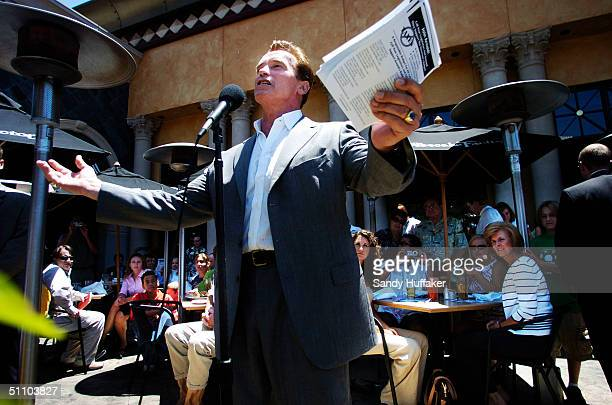 California Governor Arnold Schwarzenegger speaks to the media at a restaurant known as the Cheesecake Factory July 21 2004 in San Diego California...