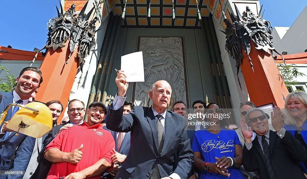 California Governor Jerry Brown, holds up AB1839, the California Film and Television Job Retention Act, after signing the legislation into law, in front of TCL Chinese Theatre in Hollywood, California, September 18, 2014 while surrounded by state and local politicans and movie industry and union figures. The legislation increases Californias $100 million Film and TV Tax Credit Program to $330 million a year in an effort to keep entertainment production, and the jobs that go with, in California. AFP PHOTO / Robyn Beck