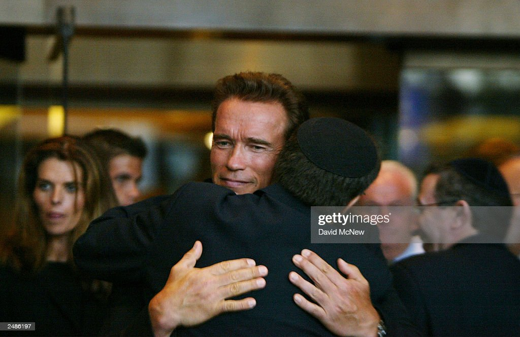 California gubernatorial candidate <a gi-track='captionPersonalityLinkClicked' href=/galleries/search?phrase=Arnold+Schwarzenegger&family=editorial&specificpeople=156406 ng-click='$event.stopPropagation()'>Arnold Schwarzenegger</a> hugs a Rabbi after lighting Jewish candles in honor of those who died in the September 11 terror attacks on the second anniversary at the Simon Wiesenthal Center September 11, 2003 in Los Angeles, California. Arnold's wife Maria Shriver is visible at left. Schwarzenegger is running to replace current governor Gray Davis in the October 7 recall election.