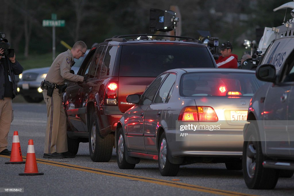 A California Highway Patrol officer checks the identifications of residents being allowing to pass through a roadblock on Highway 38 toward the Big Bear Lake, California as a standoff with the former Los Angeles police officer who is now-quadruple murder suspect Christopher Dorner continues, near San Bernardino, California February 12, 2013, some 46 miles (75 km) from the San Bernardino Mountains near Big Bear, California where Dorner, a former US cop, has barricaded himself in a cabin and exchanged gunfire with police who have the cabin surrounded. AFP PHOTO / David McNew