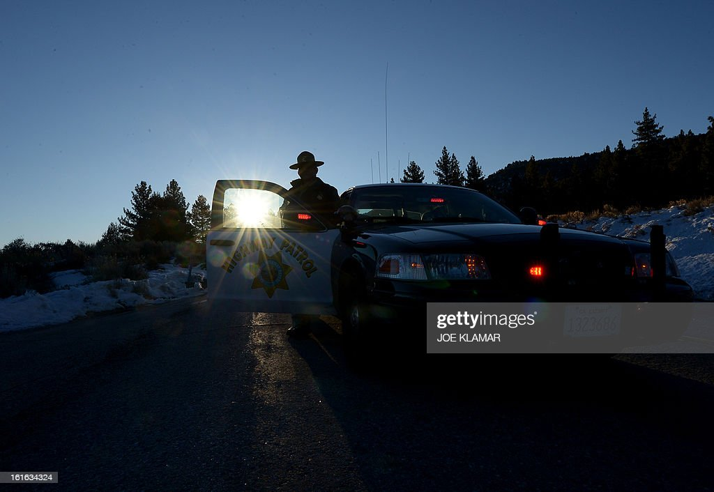 A California Highway Patrol officer guards a roadblock in early hours February 13, 2013 on Highway 38 near the Big Bear Lake in the San Bernardino Mountains of California, near the location where suspected cop killer Christopher Dorner is believed to have been killed earlier in a shoot-out at a cabin.