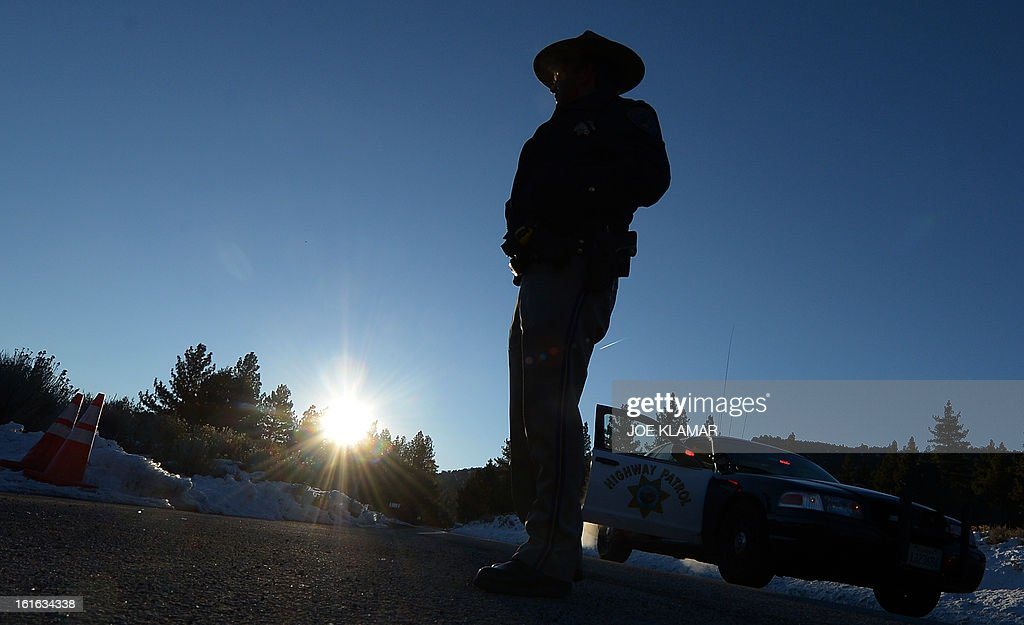 A California Highway Patrol officer guards a roadblock in early hours February 13, 2013 on Highway 38 near the Big Bear Lake in the San Bernardino Mountains of California, near the location where suspected cop killer Christopher Dorner is believed to have been killed earlier in a shoot-out at a cabin. AFP PHOTO / JOE KLAMAR