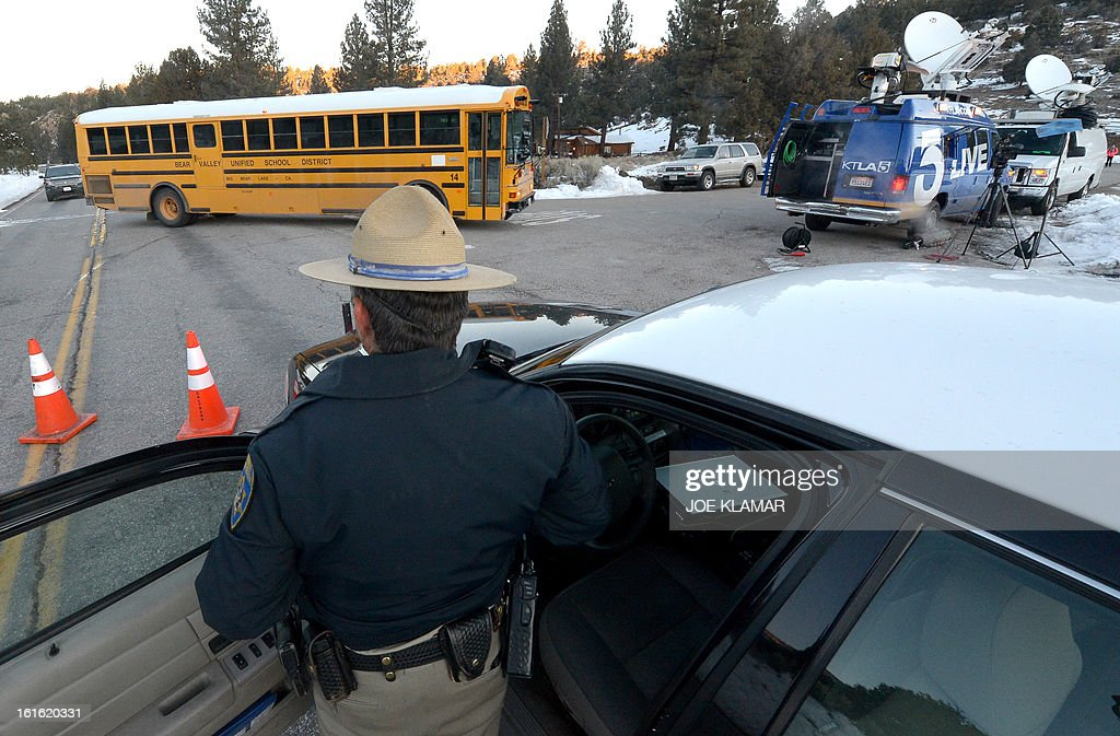 A California Highway Patrol officer guards a roadblock on Highway 38 near Big Bear Lake, California, on February 13, 2013 during a standoff with the former Los Angeles police officer Christopher Dorner. Authorities on Wednesday examined human remains found in a burned out mountain cabin to determine whether they belong to Dorner, a fugitive ex-cop wanted in at least four murders. Police discovered the remains in the cabin's charred ruins after a chase ended in a shootout with police and fire near Big Bear in the snow covered mountains east of Los Angeles where Dorner was thought to have taken refuge.