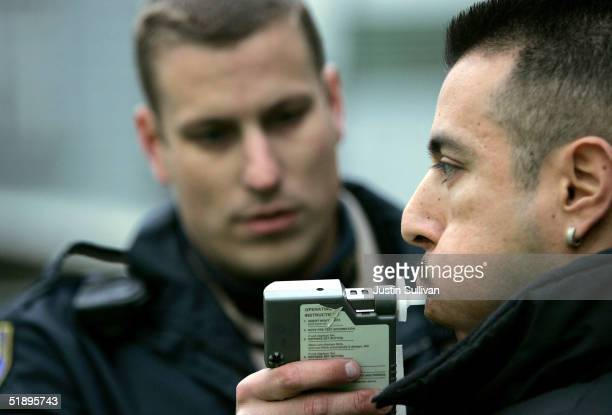 California Highway Patrol officer Mark Rossetti administers a breathalizer test to a man at a sobriety checkpoint December 26 2004 in San Francisco...