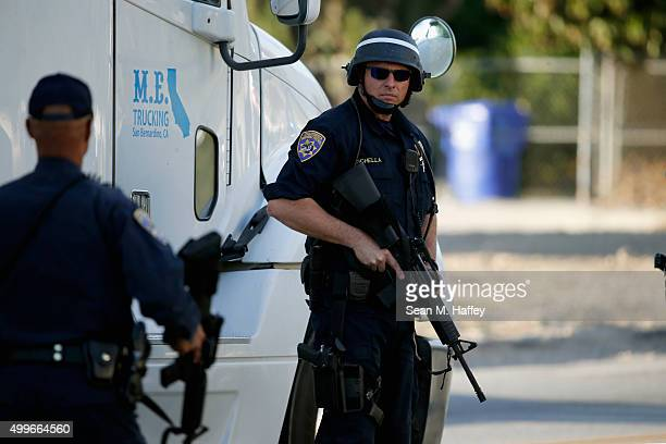 California Highway Patrol officer stands with his weapon as authorities pursued the suspects in a shooting that occurred at the Inland Regional...