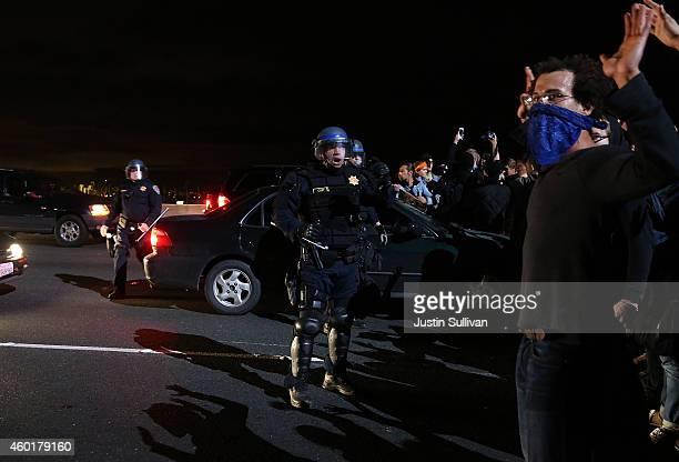 California Highway Patrol officers confront protesters who were blocking interstate 80 during a demonstration over recent grand jury decisions in...