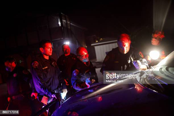 California Highway Patrol officers gather around Sergeant Rivers second from right as they study the neighborhood maps so that they can go door to...