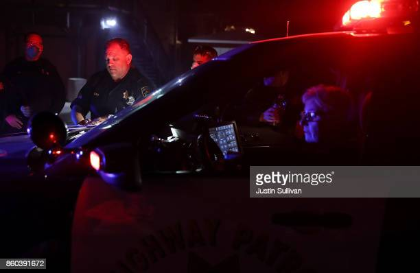 California Highway Patrol officers look over a map of a neighborhood as they go doortodoor to ask residents to voluntarily evacuate as a wildfire...