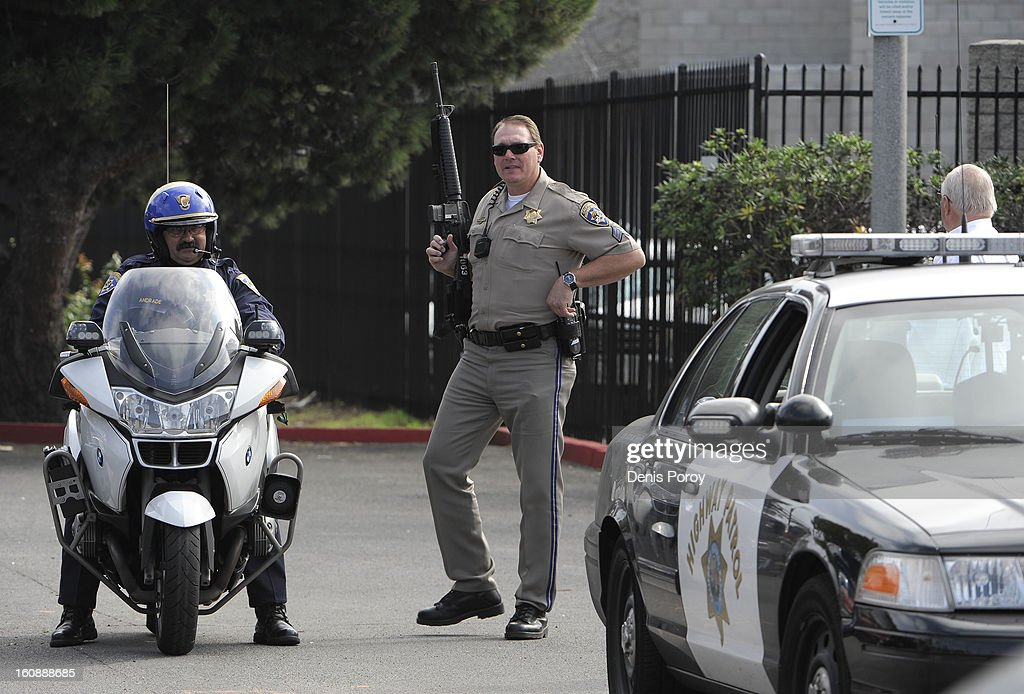California Highway Patrol officers stand guard as police officers search for suspect, former LAPD officer Christopher Jordan Dorner, at a hotel in the Point Loma area February 7, 2013 in San Diego, California. A manhunt is underway for Dorner, who is suspected of shooting at police officers in the Los Angeles area.