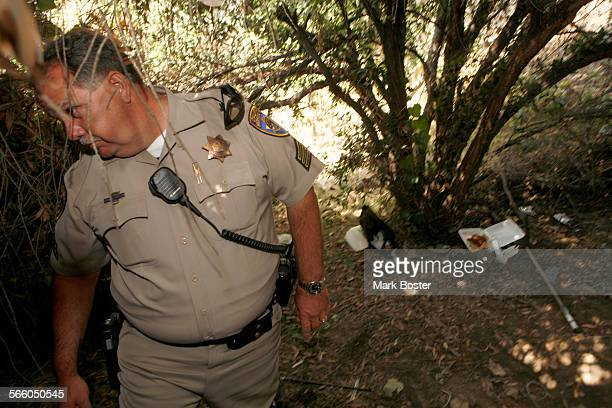 California Highway Patrol Sergeant Adam Christin checks out the location in Long Beach where five people were found was found shot to death in what...
