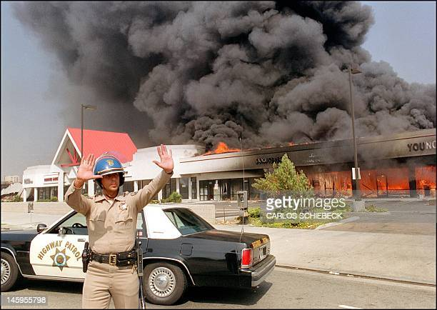 A California Highway patrolman directs raffic around a shopping center engulfed in flames in Los Angeles 30 April 1992 Riots broke out in Los Angeles...