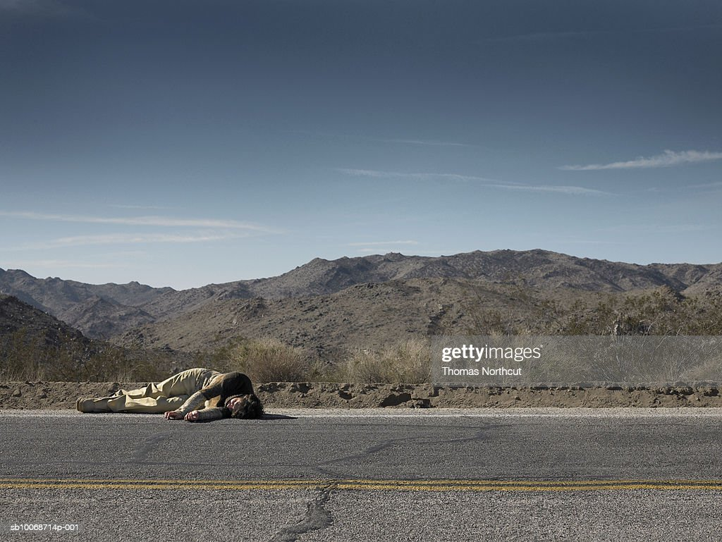 USA, California, Idyllwild, Man lying on roadside in desert landscape : Stock Photo