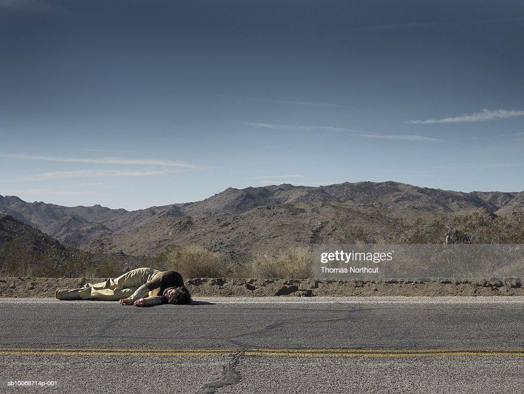 USA, California, Idyllwild, Man lying on roadside in desert landscape