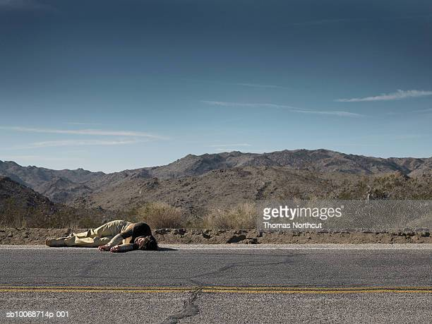 USA, California, Idyllwild, Man lying on roadside in desert landscape