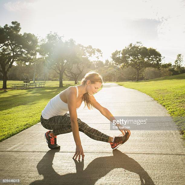 USA, California, Irvine, Woman stretching in park