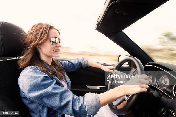 USA, California, Joshua Tree National Park, Young woman driving convertible