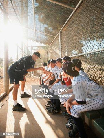 USA, California, Ladera Ranch, coach training little league baseball team (10-11) on dugout