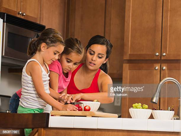 USA, California, Ladera Ranch, Mother and children (6-7, 8-9) preparing food in kitchen