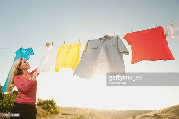 USA, California, Ladera Ranch, Woman hanging laundry on clothesline