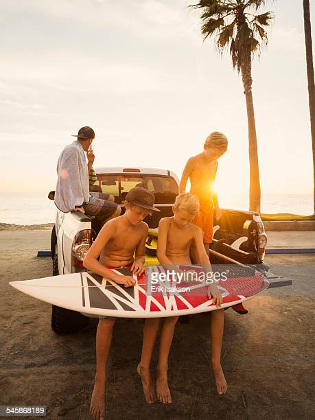 USA, California, Laguna Beach, Boys (6-7, 10-11, 14-15) waxing surfboard at sunset