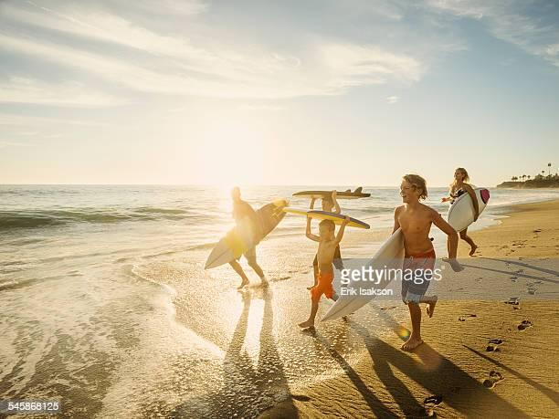 USA, California, Laguna Beach, Family with three children (6-7, 10-11, 14-15) with surfboards on beach