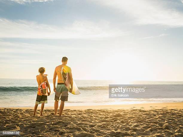 USA, California, Laguna Beach, Father and son (14-15) looking at sea
