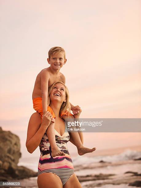 USA, California, Laguna Beach, Mother carrying son (6-7) on shoulders outdoors