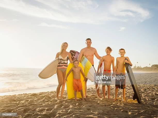 USA, California, Laguna Beach, Portrait of family with three children (6-7, 10-11, 14-15) with surfboards on beach