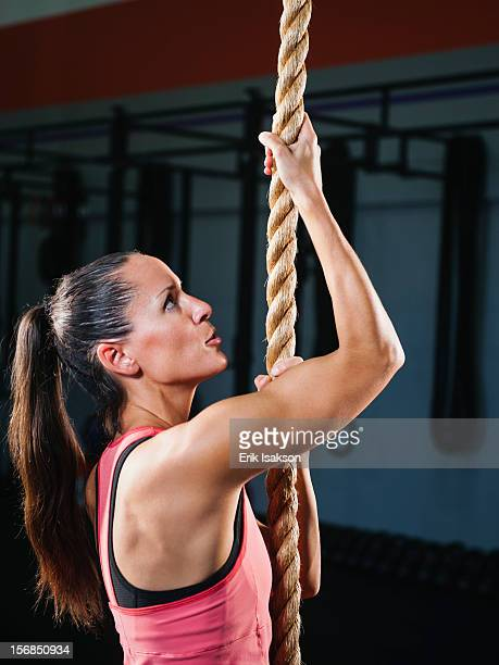 USA, California, Laguna Niguel, mid-adult woman climbing up rope