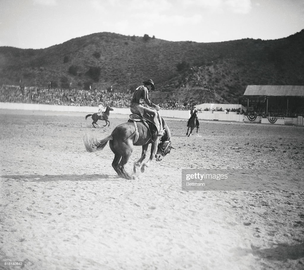 Living Dynamite Earl Thode of Casa Grande Arizona sticks to the back of 'Tumble Weed' a bucking bronco for the required ten seconds to win the...