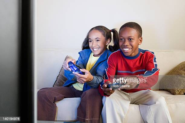 USA, California, Los Angeles, Brother and sister (10-13) playing video game