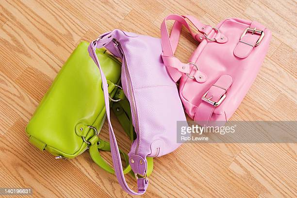 USA, California, Los Angeles, Close up of three colorful purses on parquet floor