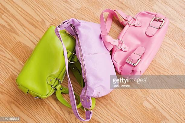 USA, California, Los Angeles, Close up of three colorful purses on parquet floor