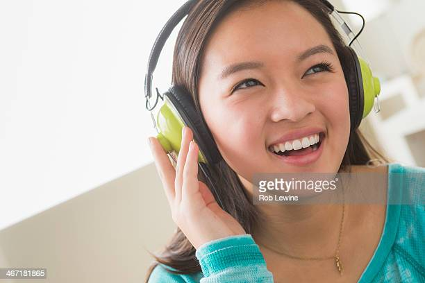USA, California, Los Angeles, Girl (16-17) listening to music wearing headphones