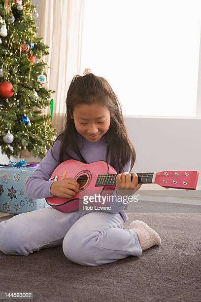 USA, California, Los Angeles, Girl (10-11) playing guitar, Christmas tree in background