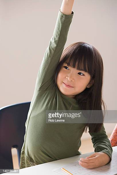 USA, California, Los Angeles, Girl (6-7) raising hand in classroom