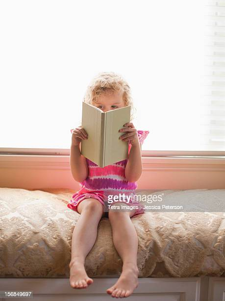 USA, California, Los Angeles, Girl sitting and reading book.