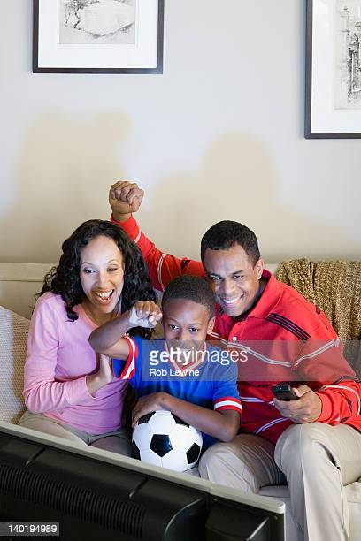 USA, California, Los Angeles, Parents with Son (12-13) watching sports on tv