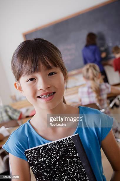 USA, California, Los Angeles, Portrait of schoolgirl holding notebook